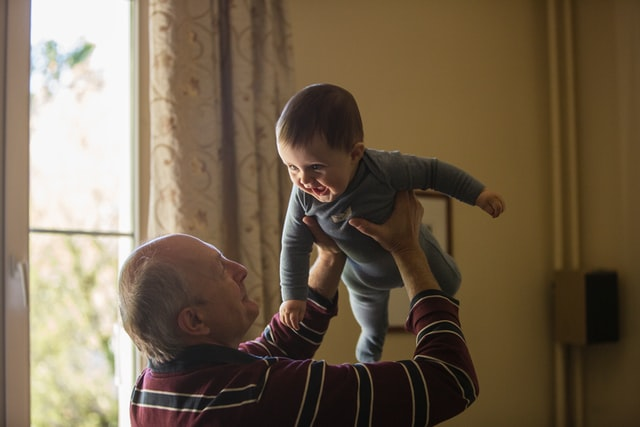 Elderly man holding a baby above his head